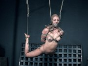 Jacey Jinx busty blonde is bound in rope with feet from the floor