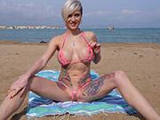 Tall bikini model wears crotchless bottoms on a public beach