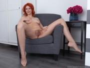 Kristina Amanda strips naked on a grey armchair