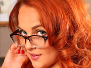 Sexy redhead in glasses and pantyhose strips in the library