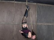 Kat Monroe in leather with high boots is bound wrapped in rope