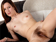 Revealing her hairy twat on the couch