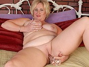 Fat mature blonde Molly spreading and toying her shaved pussy on couch