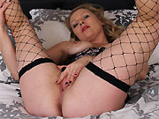 Abigail Toyne in fishnet stockings spreads on a bed