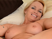 Dani Dare busty mature blonde plays nude on a bed