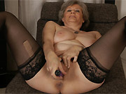 Busty mature blonde in black stockings plays a vibrator