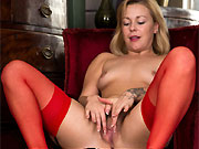 Lucy Lauren sexy blonde in red dress and stockings strips in armchair