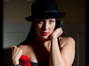 Brunette with long hair poses in a little black dress with a red rose
