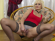 Amateur blonde milf in stockings strips in an armchair