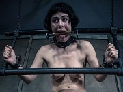 Olive Glass corset maid is bound in metal with dripping mouth gag