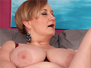 Mature blonde with massive boobs shows a striptease