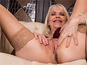 Margaret Holt mature blonde in stockings posing in armchair