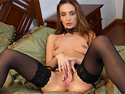 Hazel Dew in black stockings spreads on big bed