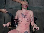 Paige Pierce is bound in rope and clamped with toying in dungeon
