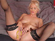 Kathy Anderson in black stockings spreads on a bed