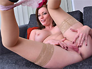 Holly Kiss in tan stockings spreads on a sofa