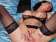 Busty tattooed mom in black stockings spreads on a bed