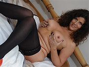 Gilly Sampson curly mom in black stockings toying on bed