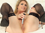 Sexy blonde in black stockings spreads on bed