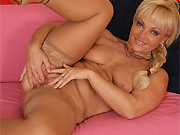 Mature blonde in tan stockings shows a twat close up