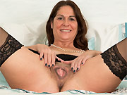 Horny milf in black stockings shows a hairy twat