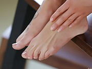 Tanned brunette gives a footjob and gets banged