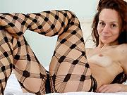 Anee Ocean redhead milf in fishnet pantyhose strips on bed