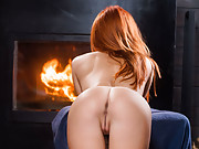 Fantastic busty redhead strips next to fire