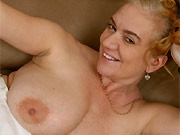 Lily May mature blonde with massive boobs poses in stockings