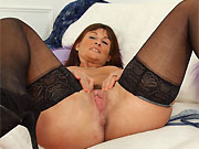 Amateur milf brunette in black stockings stripping on sofa
