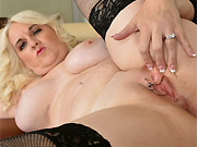 Anna Moore bigboobs blonde in black stockings poses on sofa