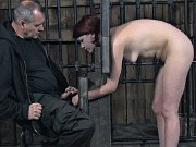 Lia Katt redhead is bound in stocks for spanking and bdsm sex