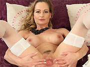 Sexy milf blonde in white stockings posing on a bed