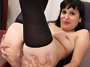 Penelope Patterson dark-haired milf in stockings strips on table