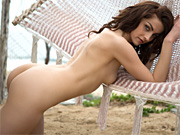 A brunette babe exposes her sexy curves on the beach