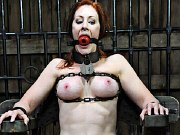 Catherine de Sade masked redhead is bound in metal for spanking