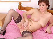 Horny mature in black stockings spreads on a bed