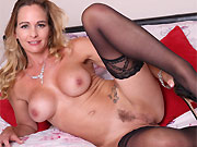 Elegant Eve busty blonde in black stockings strips on bed