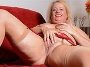 Erotica Ann busty mature blonde in stockings poses on sofa
