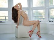 Brunette Aidra Fox stripping and posing in red high heels