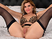 Alby Daor in lingerie and black stockings spreads on bed