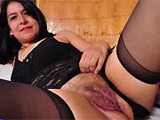 Dark-haired mom in black lingerie and stockings strips