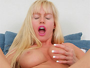Busty milf blonde plays with dildo on a bed