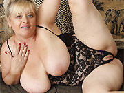 Horny mature blonde with massive boobs poses on a sofa