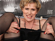 Horny mature blonde in black stockings toying on chair