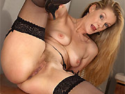 Mature blonde Caroline in black dress and stockings strips