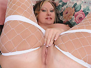 Busty milf blonde Mary Jane poses in fishnet stockings