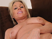 Mature blonde Payton Hall in tan stockings plays pussy