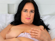 Busty dark-haired mom Ria Black in lingerie poses on bed