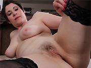 Busty milf Sadie Jones strips and poses in black stockings